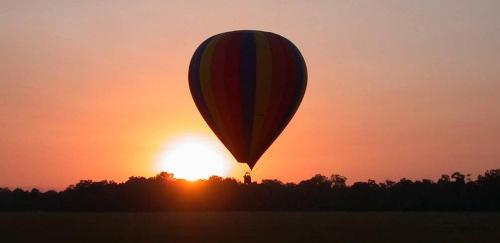 The magic in a day is easy to find when it begins with a golden sunrise photographed from a hot air balloon flying low over Africa's Serengeti.
