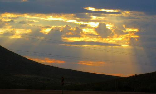 I took this sunrise shot while driving across West Texas. At first I hated the power lines that make it look flawed. These days I look at it a bit differently. How about you?  -- Photo by Pat Bean