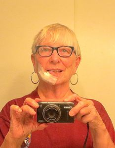 A selfie showing my bandaged face after a basal cell carcinoma was removed. I drank my coffee this morning through a straw. The big bandage, thankfully, comes off tomorrow and then there is just the tape over the stitches.-- Selfie by Pat Bean
